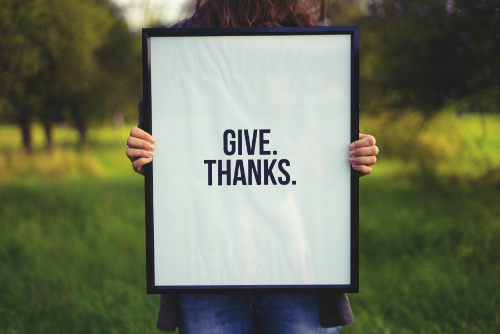person holding give thanks sign